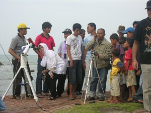 Bu Lily, one of the teacher look on the eclipse through the telescope